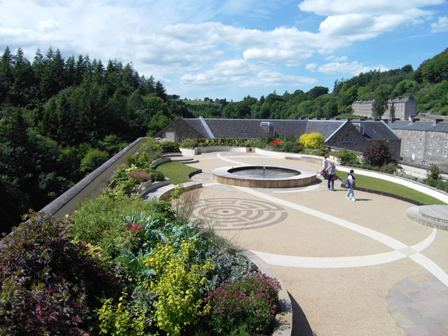 New Lanark Roof Garden with visitors and view towards New Lanark Mill Hotel